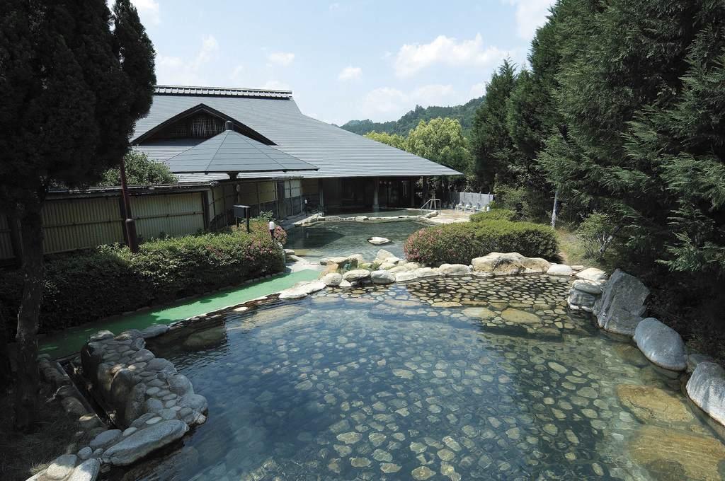 源泉かけ流し大露天風呂。男女合わせて11の浴槽があり一度に500名が入浴可能。  利用時間6:00〜22:00