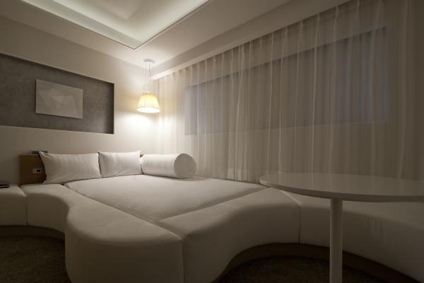【大きなベッド】ベッドとソファーが1つになった、白を基調とした落ち着いた雰囲気の客室