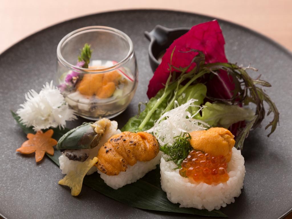 ウニと鮑の「旬一皿」。手前の握りは向かって左から鮑、炙りウニ、ちらし寿司風。左奥が水貝仕立て。