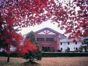 秋のもみじに囲まれるホテル外観