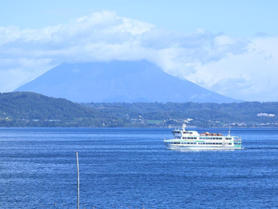 青空が映る洞爺湖に、ボートの白が映える景色。