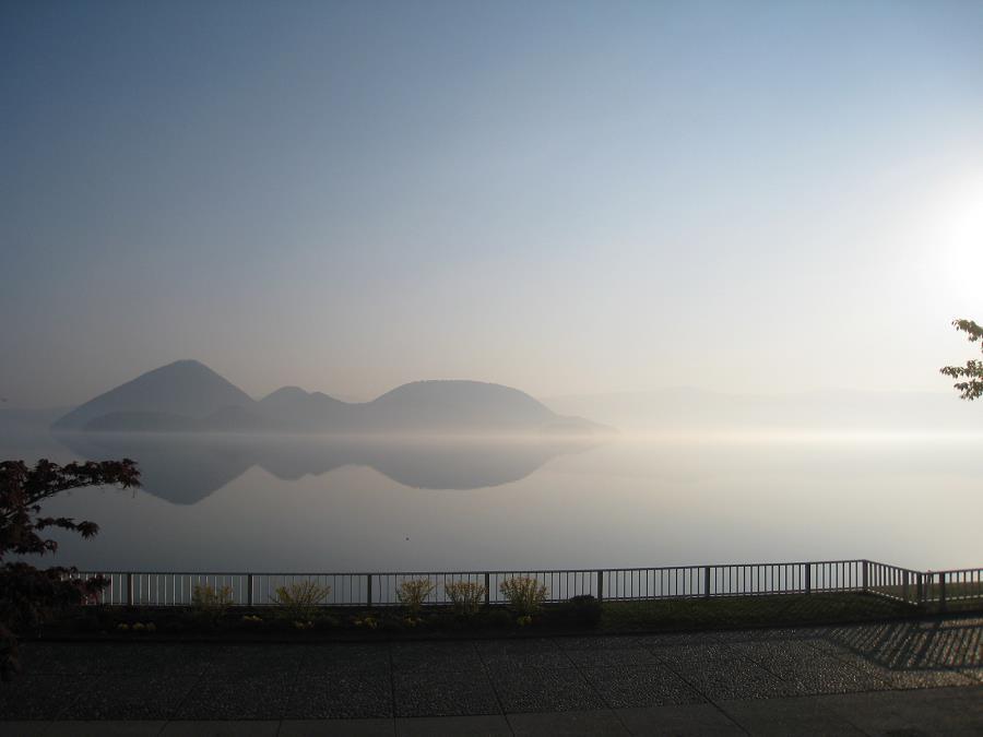 朝もやで湖面に中島が映り、朝の光が幻想的な風景を作り出します。