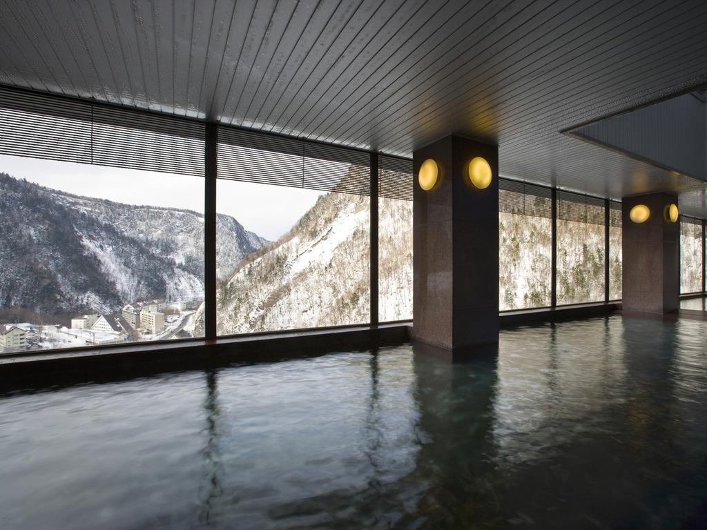 【展望大浴場 黒岳(冬)】7階に位置し、巨大なガラス窓から見下ろす絶景が楽しめます