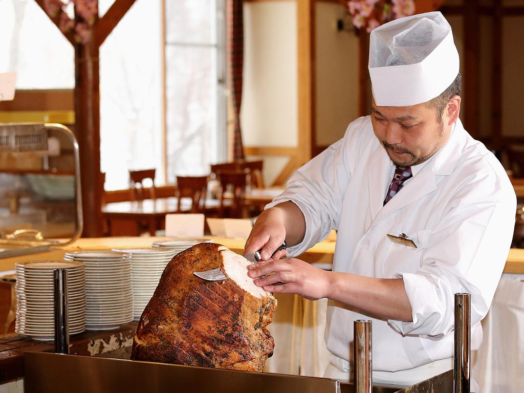 【夕食バイキング】大きな「豚塊肉の峡谷焼き」を目の前で切り分ける、バイキング実演コーナー