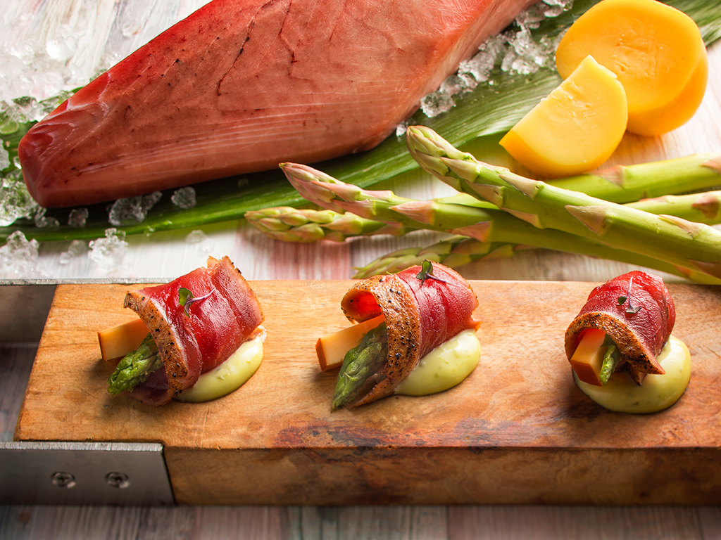 【青函市場・朝食一例】炙りマグロとスモークチーズのアスパラ巻きにジェノベーゼソースを添えて。